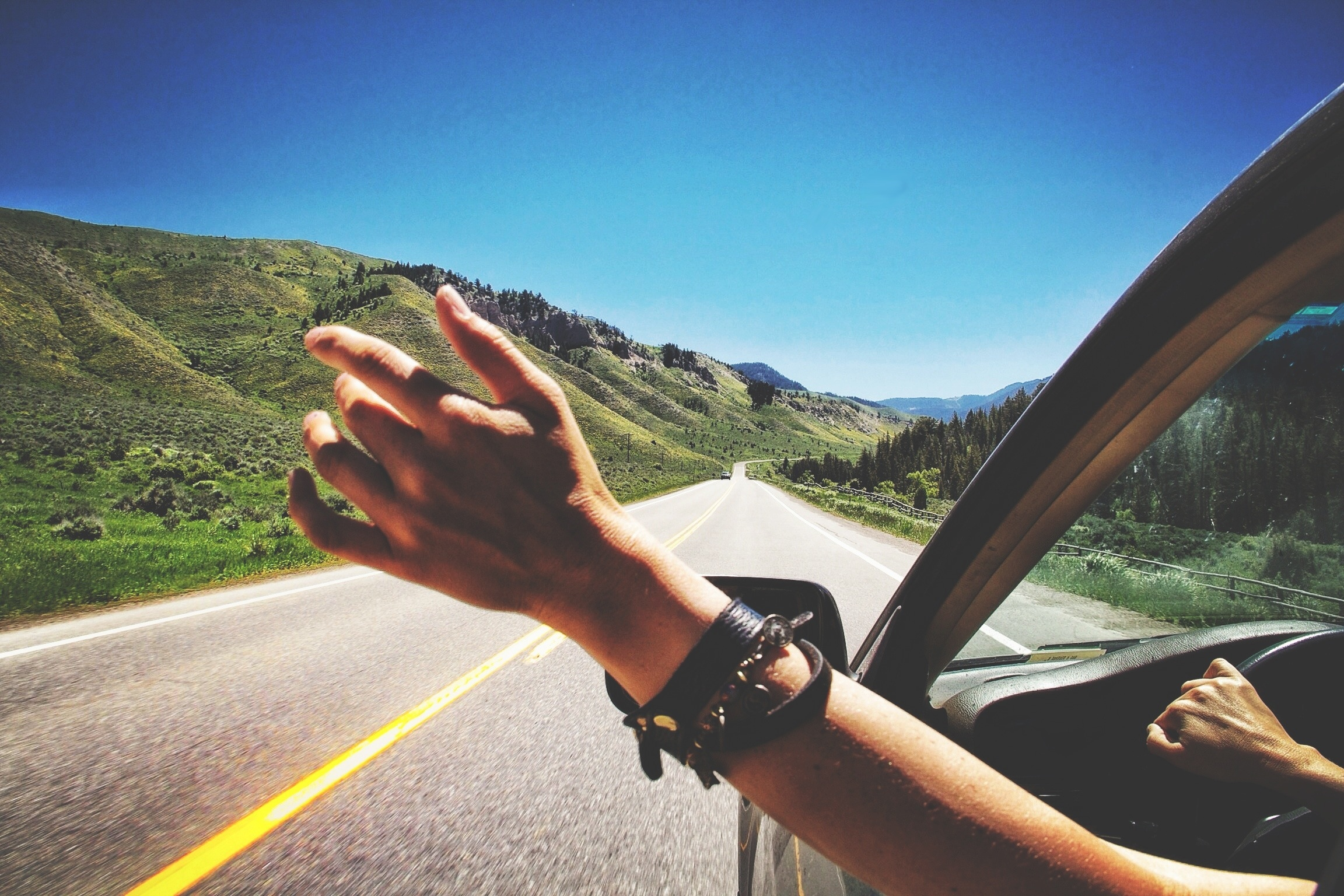 Hand out car window on open road