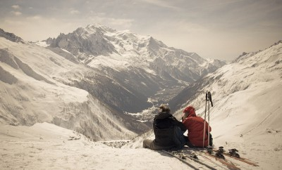 Two people sitting on snowy mountain