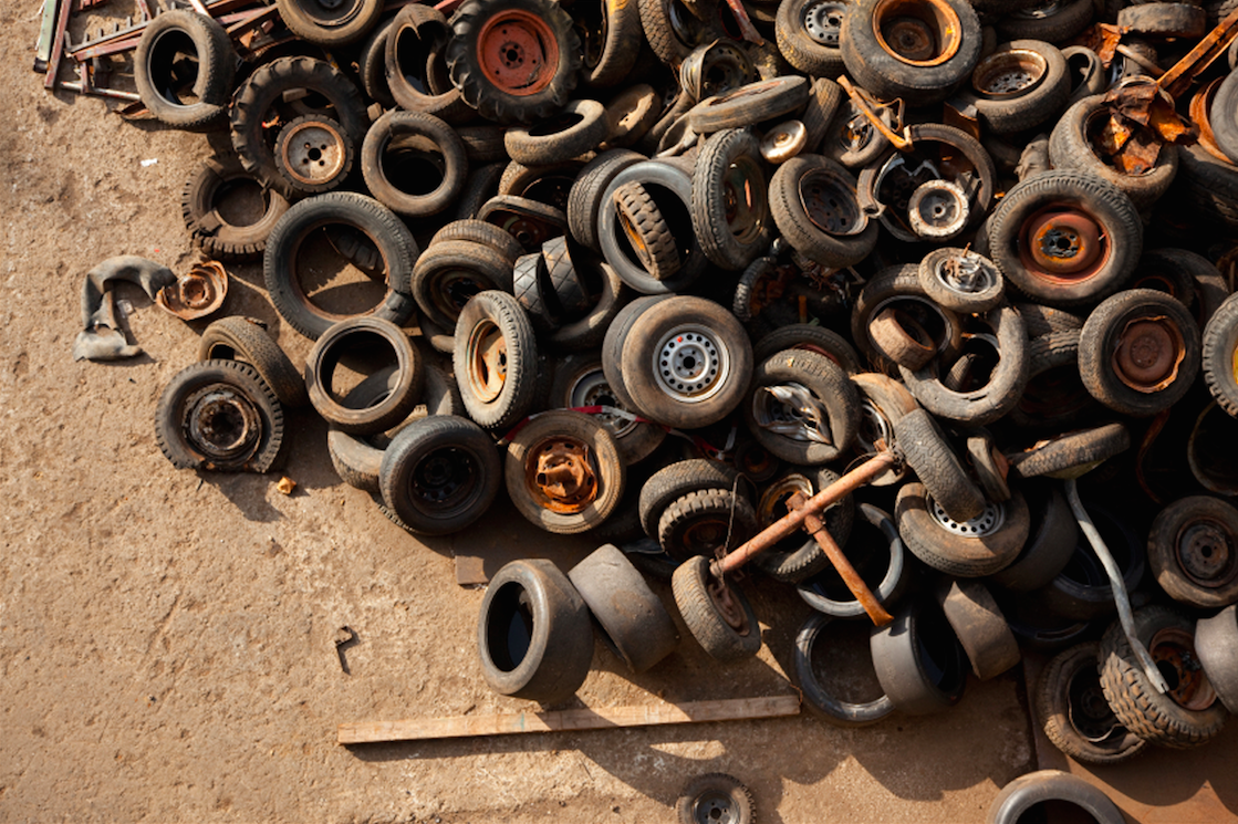 pile of worn and rusted tires and wheels