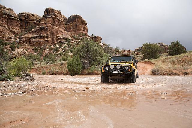 yellow SUV driving through muddy water