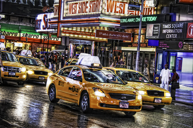time square at night with yellow taxies