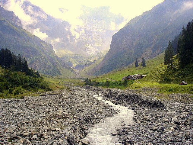 Rocky stream with the alps mountains behind it