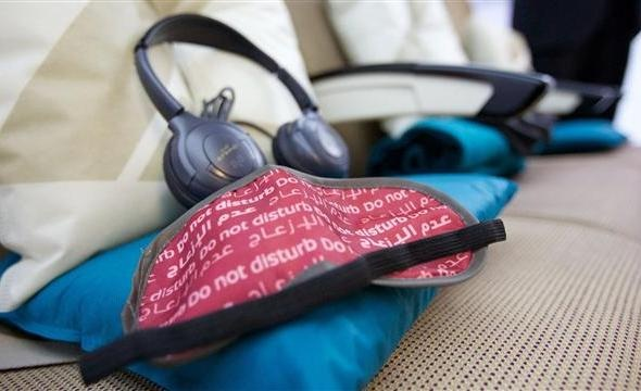 blindfold headphones and pillow on plane seat