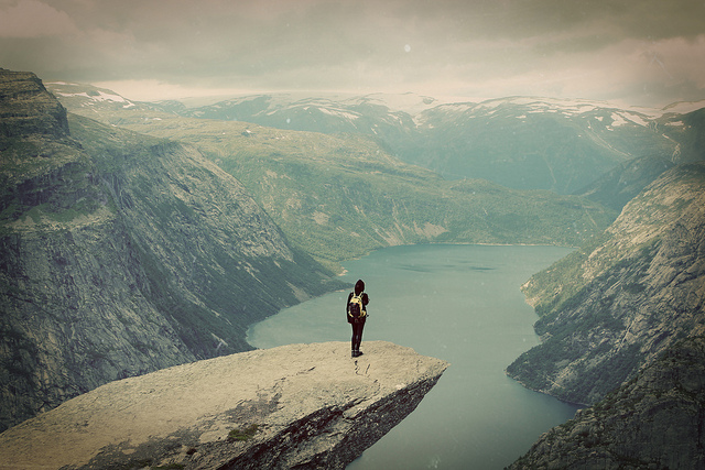 young woman standing on a rock overlook a fjord