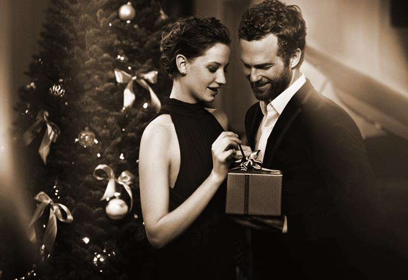 man giving woman a gift in front of a christmas tree in sepia tone