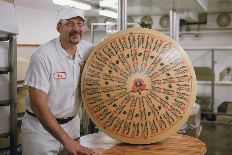 man holding giant wheel of cheese