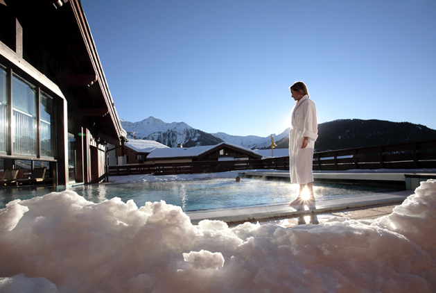 Woman standing near a hot pool outside with snow and blue skies in the french alps