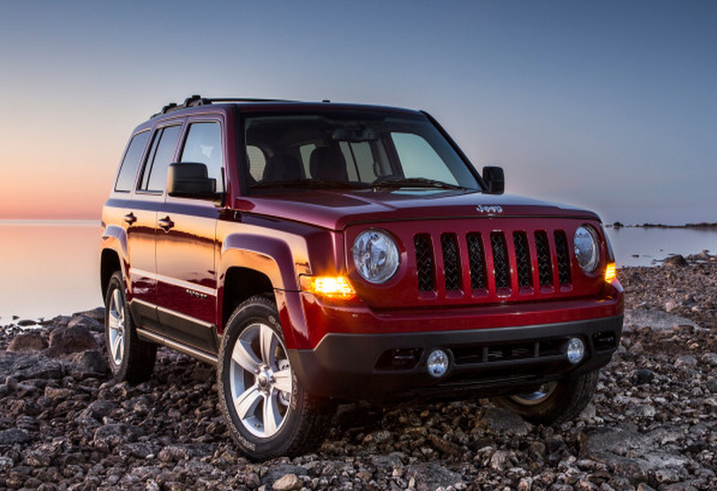 2014 red jeep patriot on rocky shore