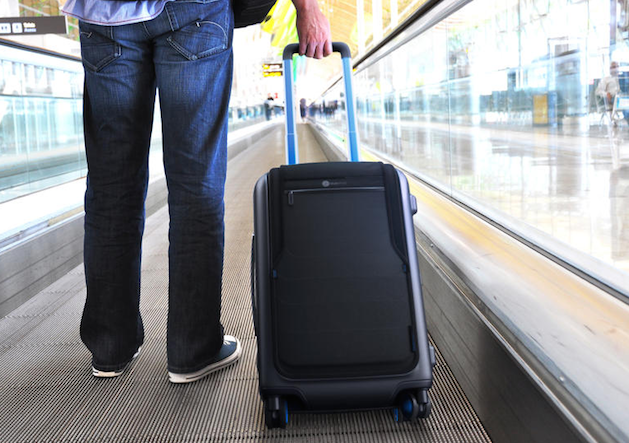 Bluesmart carryon suitcase being dragged by a man in an airport on conveyer belt