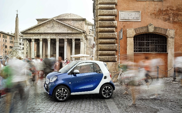 Smart Car Smart fortwo in crowded plaza with people walking