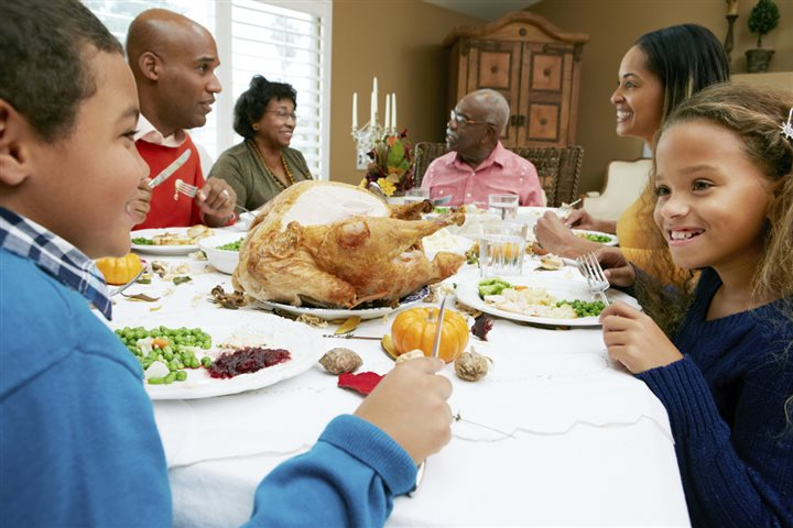 black family sitting around a table for thanksgiving