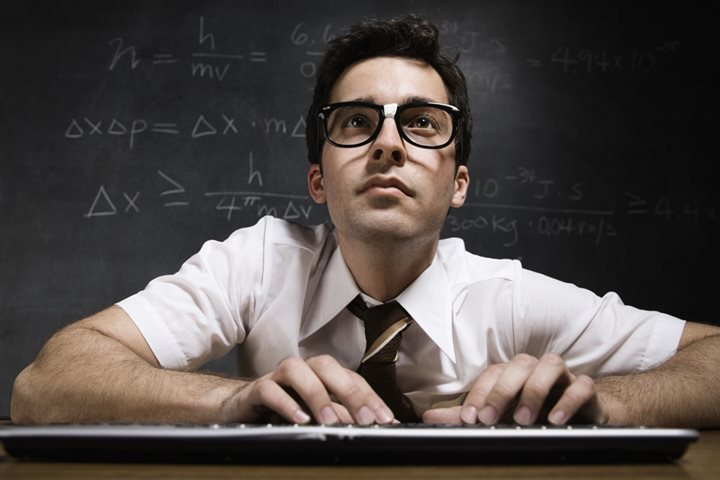 geek at a keyboard with a blackboard behind him