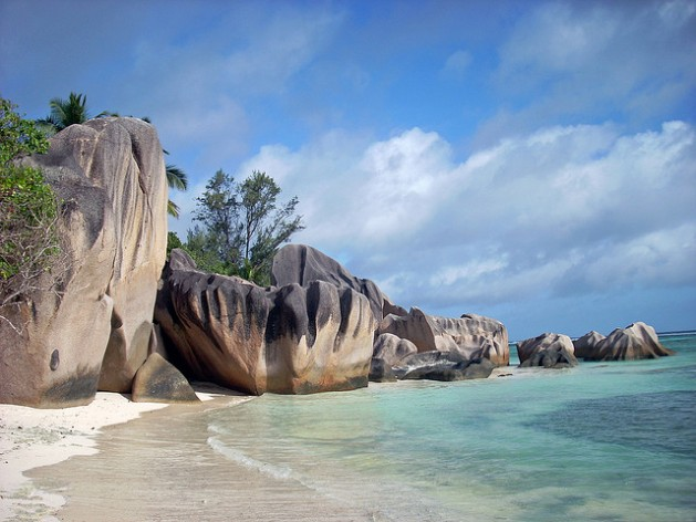 rock formations along beach with blue water