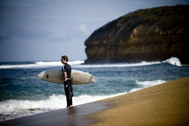 surfer on beach looking at water