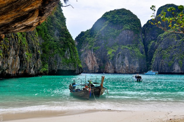 Maya Bay wooden boat on beach surrounded by rocks