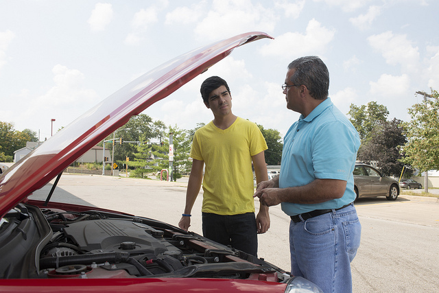young man and man looking under the hood of a red car
