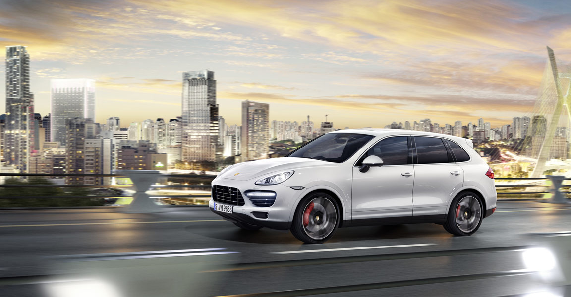 Porsche Cayenne Turbo S driving on a bridge with a city in the background