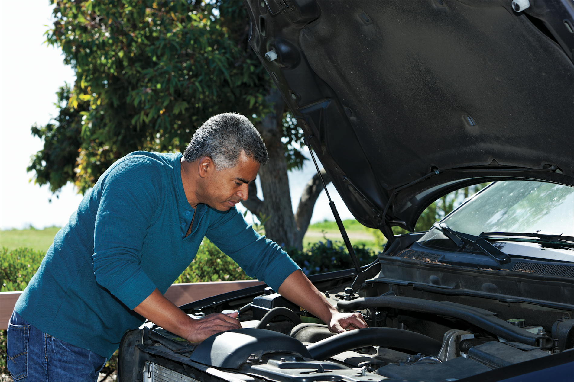 grey haired latino man fixing car