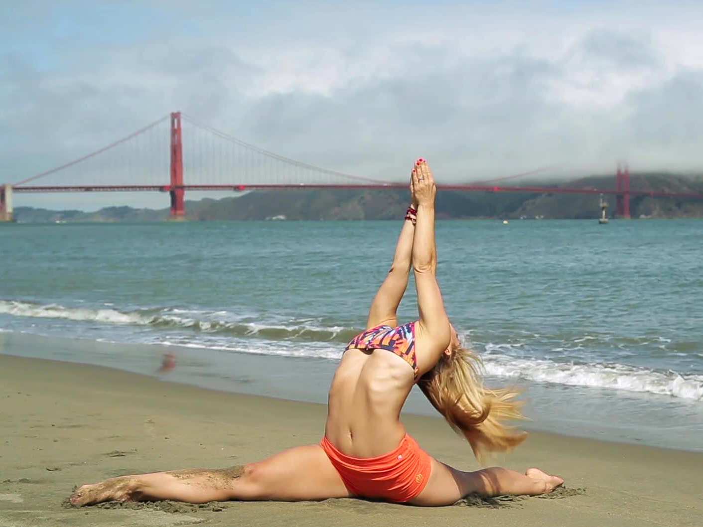 woman doing yoga on the beach in front of the golden gate bridge