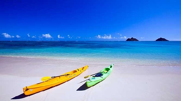 white sand beach with kayaks on sand