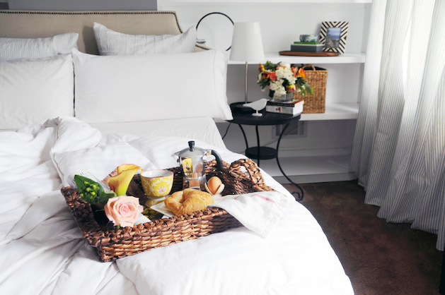 bed with white linens and breakfast