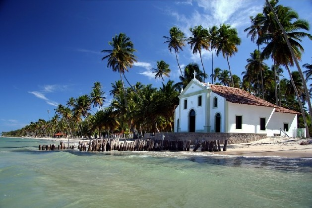 old church on beach with rotten wooden piers