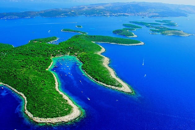 green islands in blue water with large beaches