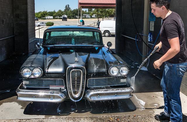 man washing classic car
