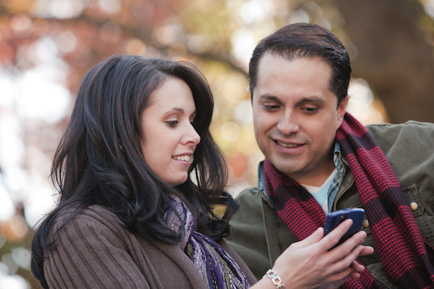 man and woman looking at a smartphone