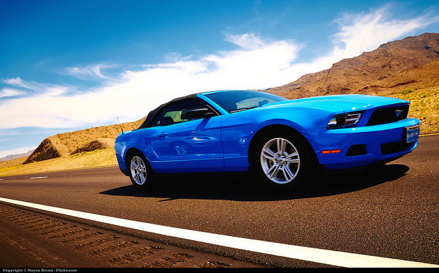 blue ford mustang driving on open road