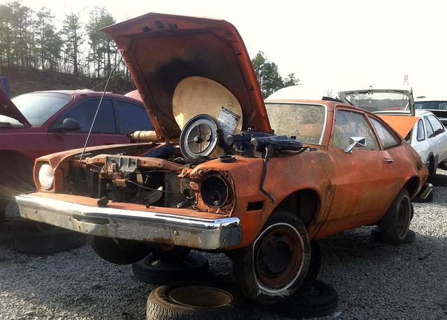 orange junk car with hood open