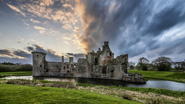 caerlaverock castle with clouds and sunset in background
