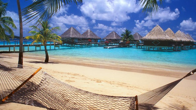 hammock on beach with thatch roofed huts