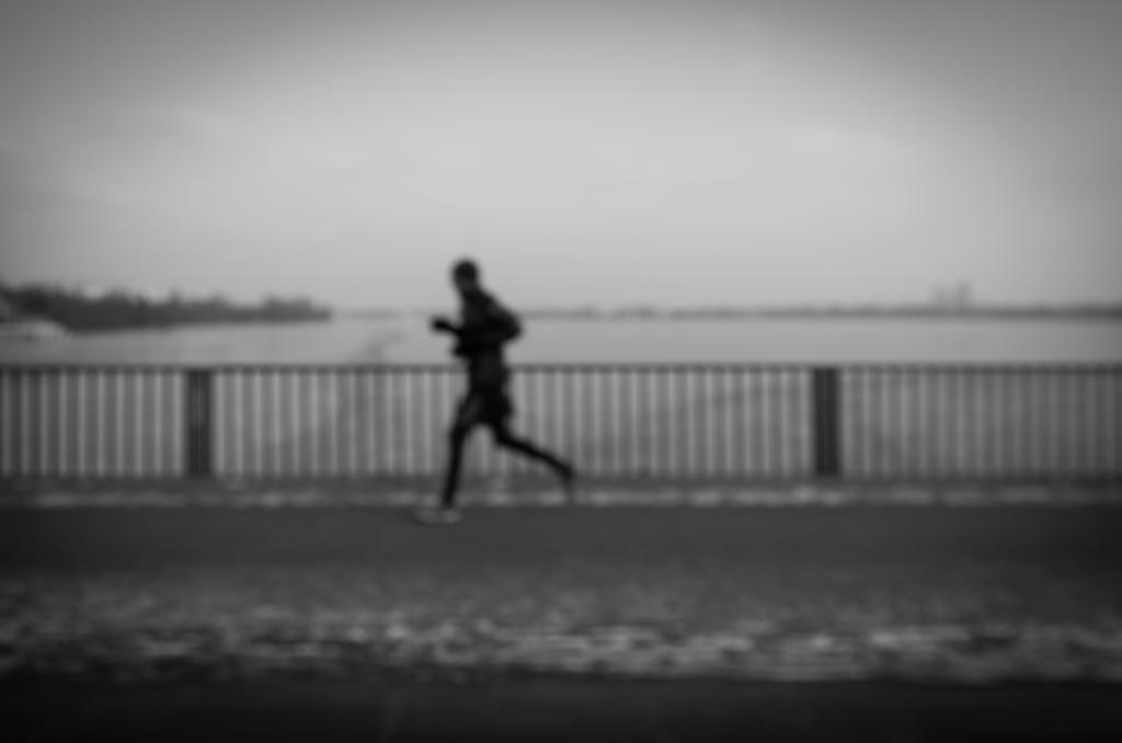 blurry photo of man running in black and white