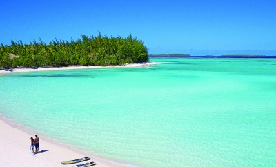people walking on white sand beach and crystal blue water