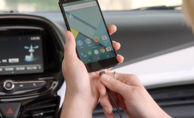 person plugging android phone into a USB cable in a car