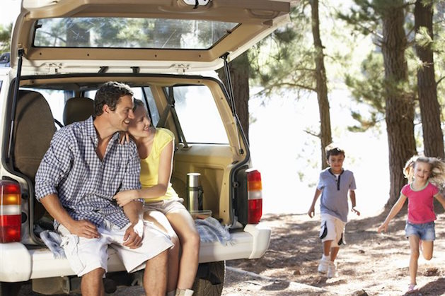 couple sitting in back of SUV while kids play in woods