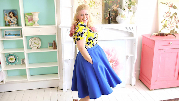 curvy woman in blue skirt with yellow floral blouse