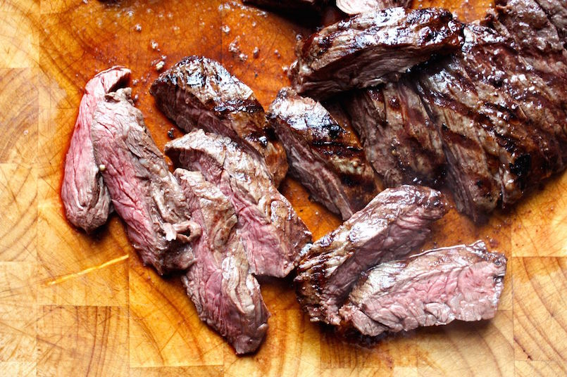 grilled skirt steak on wood cutting board