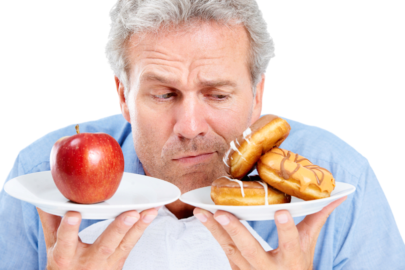 man holding an apple and doughnuts