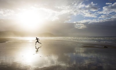 person running on beach at dawn