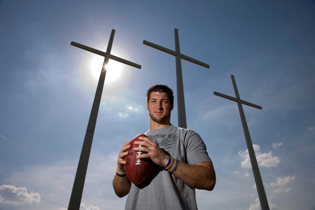 tim tebow holding football in front of three crosses