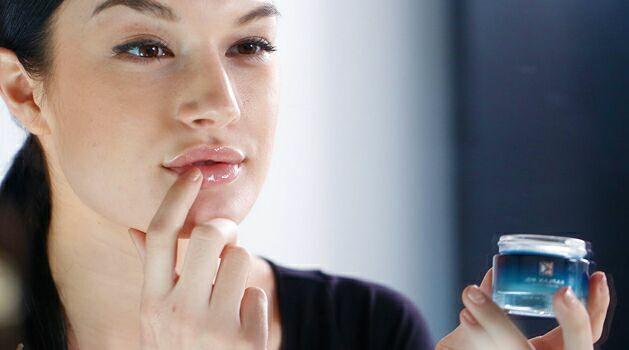 woman applying balm to lips