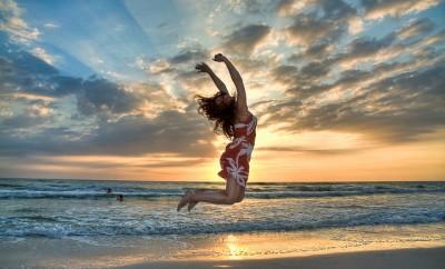 lady jumping on beach