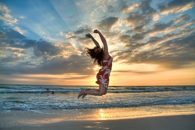 lady jumping on beach