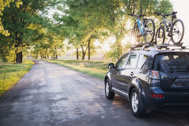 black suv with bike rack on shaded country road