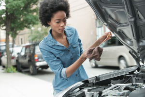black woman checking the oil in a car