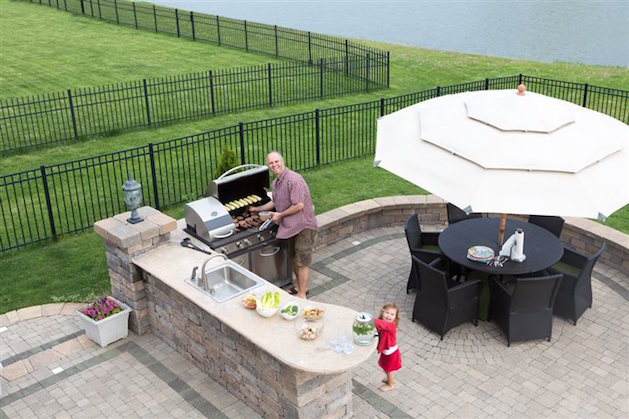 man cooking in an outdoor kitchen by water