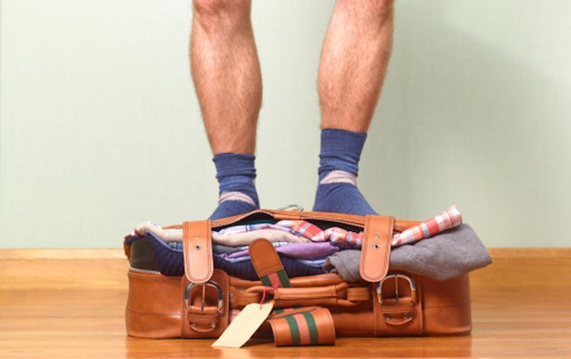overpacked suitcase with man in socks