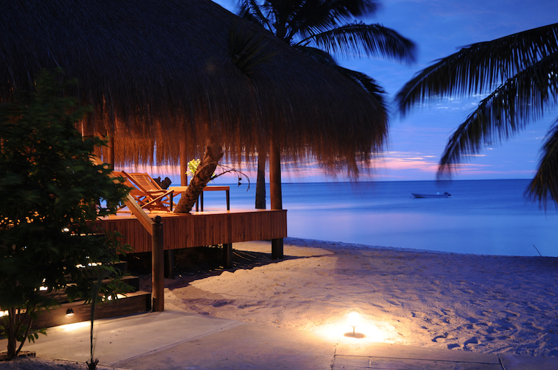thatch-roofed hut on beach at dusk